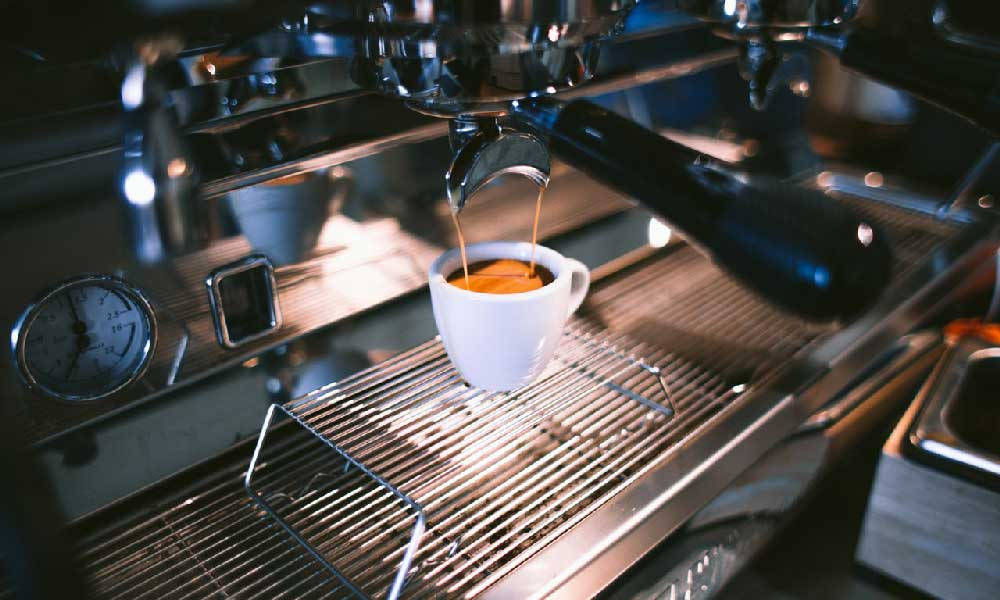 A photo of fresh espresso being poured from a commercial coffee machine