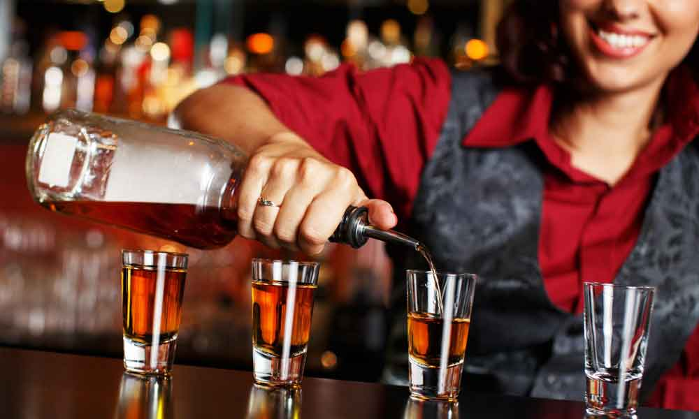 Bar manager pouring shots